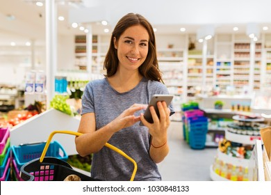 Casual young female, using her cellphone in modern market. Looking camera
