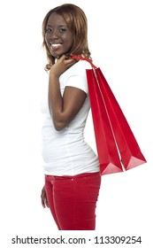 Casual young girl carrying shopping bag isolated over white background