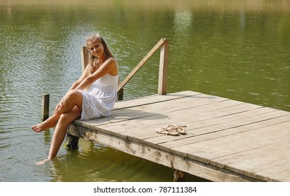 Casual young girl wearing a white sitting by the river in summer afternoon.