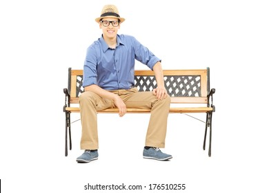 Casual young guy sitting on bench and looking at camera isolated on white background