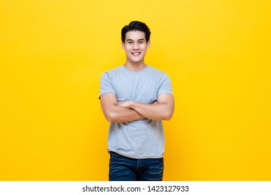 Casual young handsome man smiling and looking at camera with arms crossed isolated over yellow background