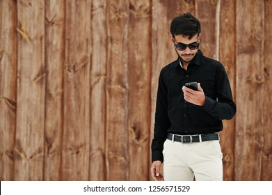 Casual young indian man in black shirt and sunglasses posed against wooden background looking at mobile phone.