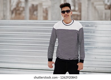 Casual young indian man in sunglasses posed against steel background.