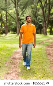 casual young indian man walking in the park and looking away
