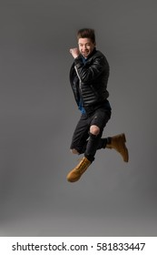 Casual young man in black jacket jumping