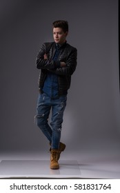 Casual young man in black leather jacket and denim jeans. low key . black background