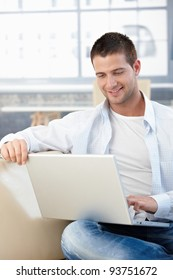 Casual young man browsing internet at home, sitting on sofa, smiling.?