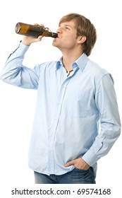 Casual young man drinking bottle of beer. Isolated on white.?