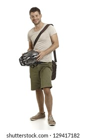Casual young man holding helmet, smiling.