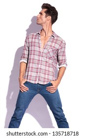casual young man holding his thumbs in his pockets with his legs spread and looking up and to a side, away from the camera. isolated on white background
