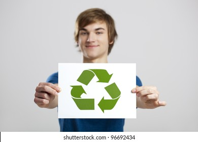 Casual young man holding a recycling sign to promote a green and better world, over a gray background