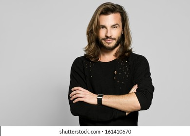 Casual young man looking at camera with arms crossed and satisfaction