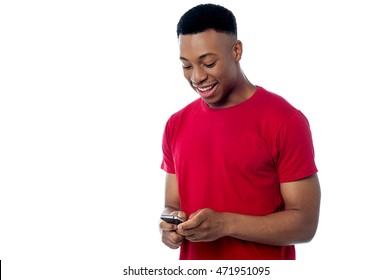 Casual young man looking into his mobile phone.