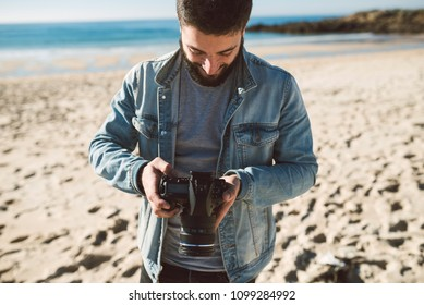 Casual young man looking a picture on his reflex camera on the beach