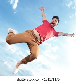 casual young man outdoor jumping with his hands in the air and screeming while looking at the camera