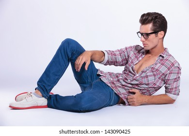 casual young man posing on the floor while looking away from the camera. on gray background