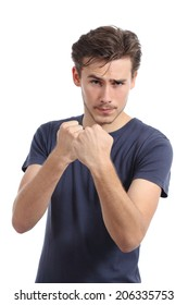 Casual young man ready to fight attacking with fist up isolated on a white background