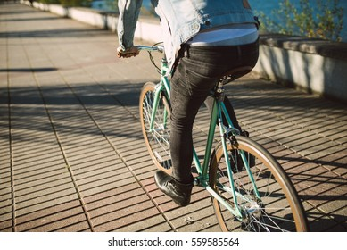 Casual young man riding his bicycle in a sunny day