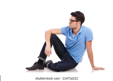 Casual young man sitting on the floor and looking to a side, away from the camera, on a white background