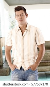Casual young man standing at home with hands in pockets, looking at camera.