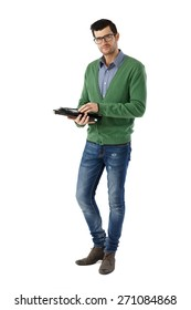 Casual young man standing over white background using tablet, looking at camera. Full-length.