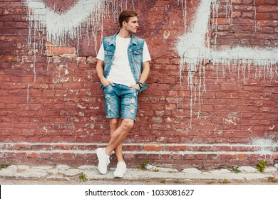 casual young man stands with his back against a brick wall