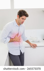 Casual young man with stomach pain standing in the kitchen at home