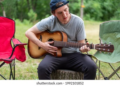 Casual young man strumming a guitar at a campsite on a summer day