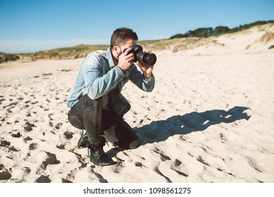 Casual young man taking a picture on the beach in a sunny day