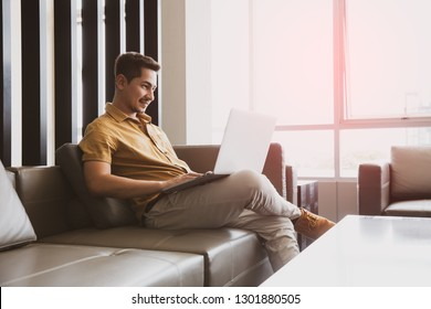 Casual young man using laptop with happy on sofa in modern office, process color.