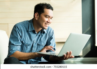 Casual young man using laptop with happy in modern office.