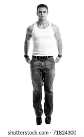 Casual young man in white undershirt and jeans. Studio shot in black and white.