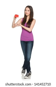 Casual young teen female showing blank credit card, in full length against white background