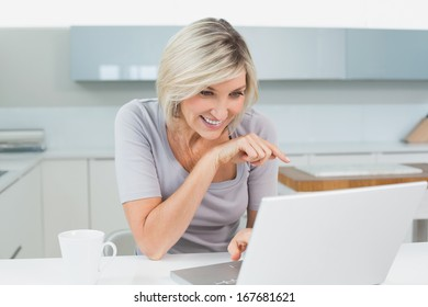 Casual young woman with coffee using laptop in the kitchen at home