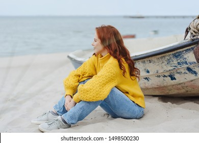 Casual young woman enjoying a misty autumn beach sitting on the sand alongside an old wooden dinghy looking out over the ocean with a smile