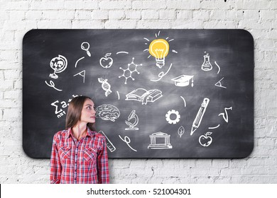 Casual young woman looking at chalkboard with education sketches. Knowledge and wisdom concept
