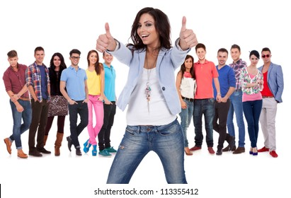 casual young woman making the thumbs up ok sign in front of a group of young people smiling