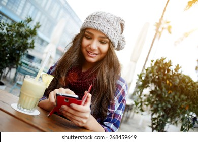 Casual young woman sending text message while sitting at a sidewalk cafe in the city, charming hipster girl enjoying a fresh cocktail during her break or holiday, female student chatting on cell phone