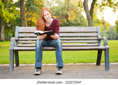 A casual young woman sitting on a bench in a park and reading her Bible.