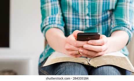 A casual young woman uses a smartphone over an open Bible at home.