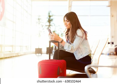 Casual young woman using her cell phone while waiting to board a plane at the departure gate.