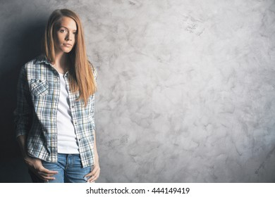 Casually dressed, attractive young woman standing against blank concrete wall. Mock up