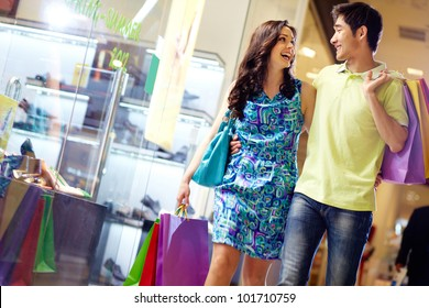 Casually dressed beautiful couple walking through the mall carrying a lot of shopping bags