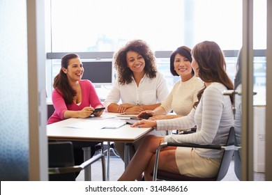 Casually dressed female colleagues talking in a meeting room