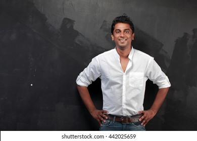 Casually dressed Indian young man against a dark wall
