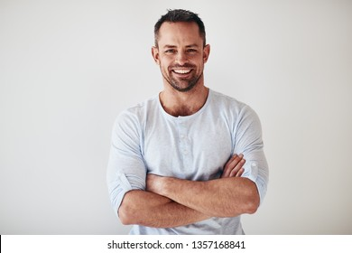 Casually dressed mature male entrepreneur smiling while standing with his arms crossed against a white background
