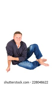 Casually dressed middle aged man smiling. Sitting on a floor barefoot man shot in vertical format isolated on white.