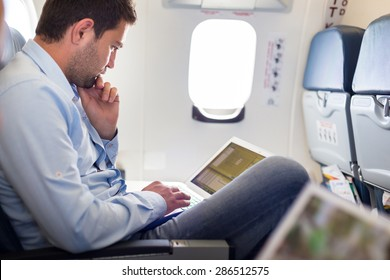 Casually dressed middle aged man working on laptop in aircraft cabin during his business travel. Shallow depth of field photo with focus on businessman eye.