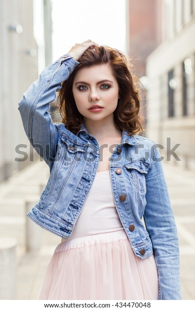 Casually dressed pretty young woman looking at camera