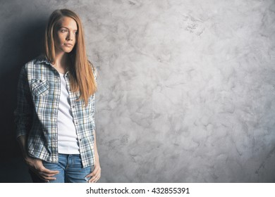 Casually dressed, thinking young woman standing against blank concrete wall. Mock up